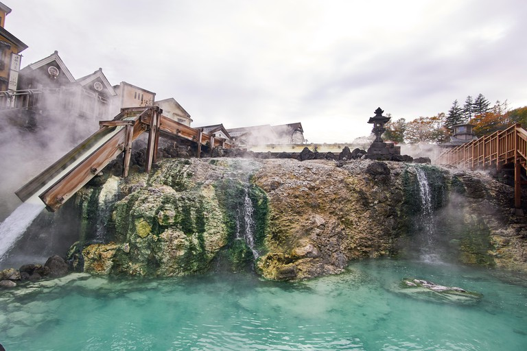 Wide angle view of the flowing sulfurous water at the hot water field (Yubatake) at Kusatsu Onsen hot spring resort in Gunma, Japan, on a cloudy day.