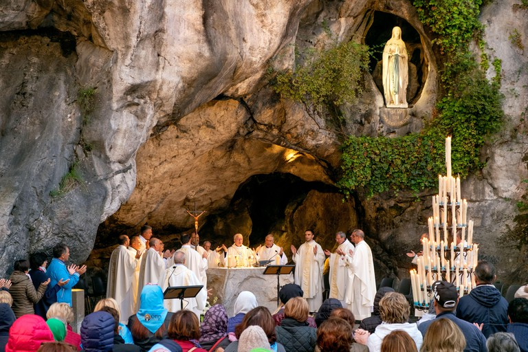 Praying at a morning mass or service, Grotte de Massabielle / Grotto of Massabielle, Sanctuary of Our Lady of Lourdes, Lourdes, Pyrenees, France