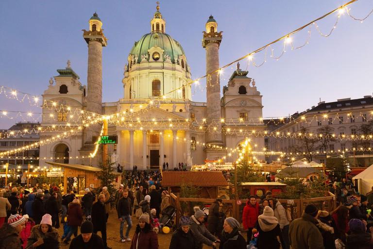 Vienna christmas market - people at the market in Karlsplatz in front of St Charles church (Karlskirche), at sunset, Vienna Austria Europe