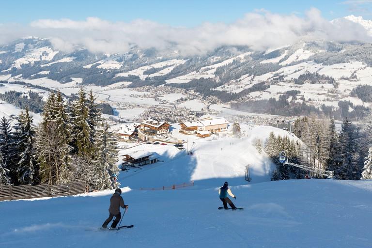 Skier and snowboarder on the slopes at Kirchberg in Tirol, part of the Kitzbuhel ski area in Austria.