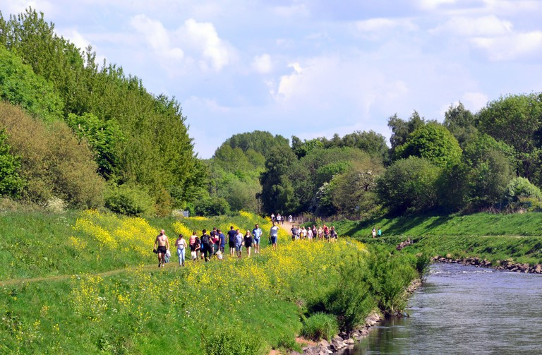 A path beside the River Mersey in Chorlton, Manchester, England, uk, is busy with walkers enjoying the sunshine on Bank Holiday Saturday afternoon, on what may be the last weekend of complete lockdown due to the Coronavirus pandemic. The uk Government has