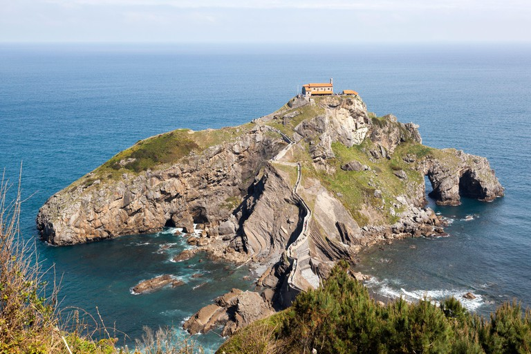San Juan de Gaztelugatxe, Basque Country, Spain. It is an islet on the coast of Biscay, connected to the mainland by a man-made bridge. On top of the