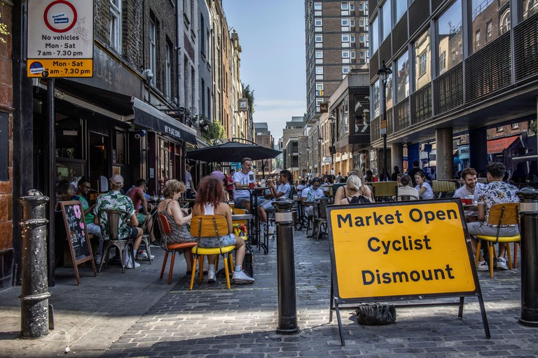 People sit outside on Berwick Street enjoying the cafe culture on a warm summers afternoon 2C9P0H8