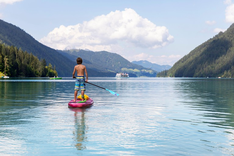 Caucasian boy on paddleboard on lake