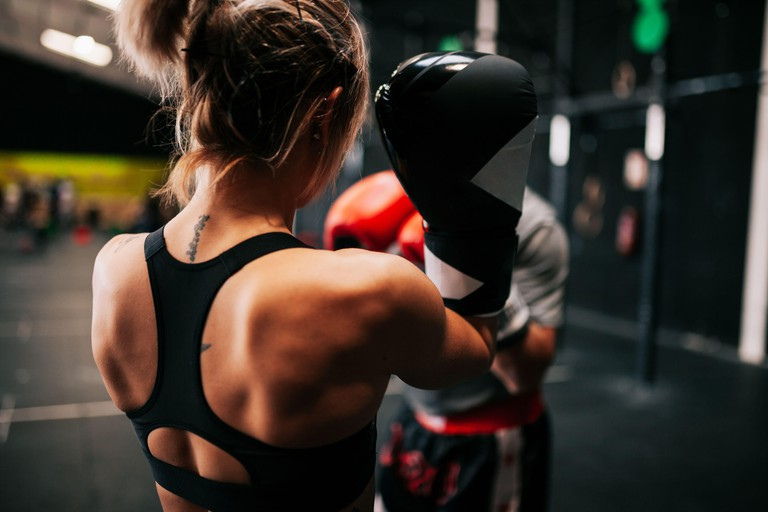 Back view of unrecognizable young sportswoman athlete in boxing gloves training fighting with anonymous professional male coach in modern gym