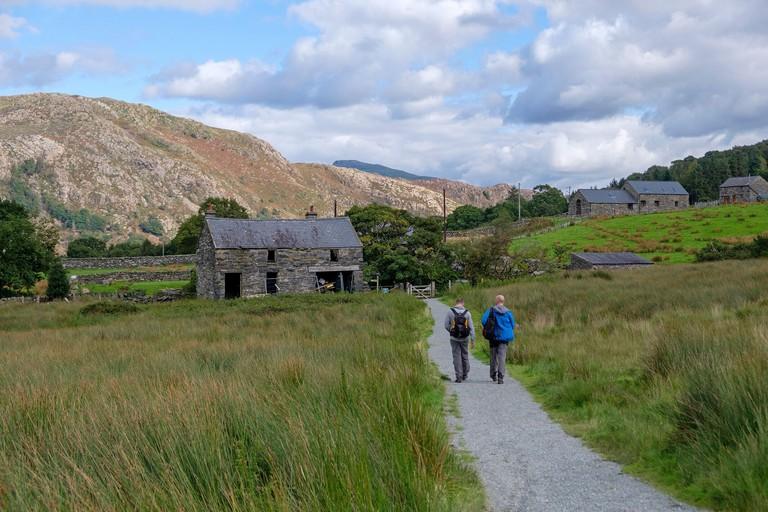 Walkers on the Slate Trail between Rhyd Dhu and Beddgelert, Snowdonia, North Wales, UK