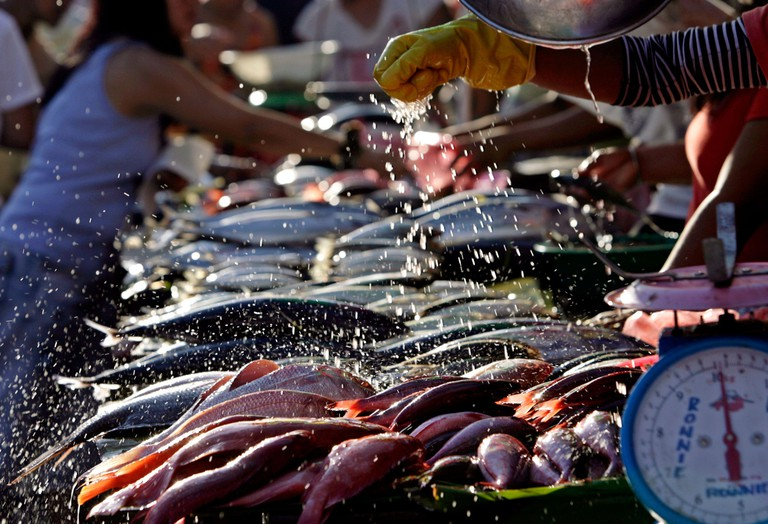 A vendor splashes water on fish for sale to keep them looking fresh at a large wet market in Manila