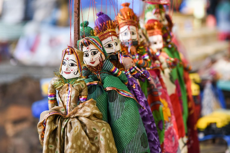 Hand made puppets attached to string in Rajasthan India. Dolls men and women face wearing traditional Indian dress Saree or Sari, Lehenga for plays