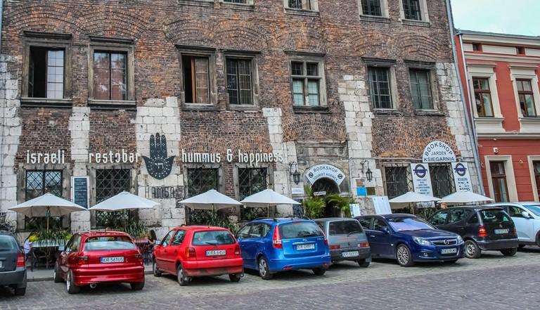 Krakow, Poland - July 29th 2018: Hamsa restaurant, bookshop and tourist agency at Szeroka street and square, Kazimierz, Jewish Quarter, Krakow, Poland