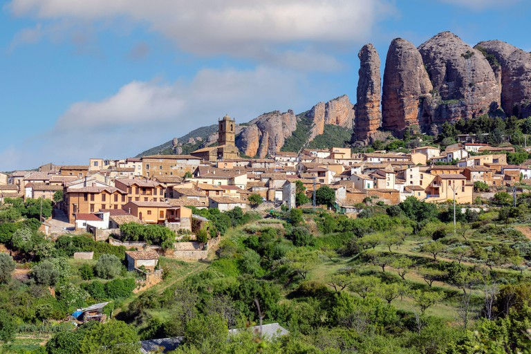Village of Aguero beneath the conglomerate rock formations of the Mallos de Riglos, Huesca Province, Aragon, Spain. The Mallos de Riglos are approxima