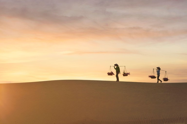 Silhouette of two women carrying baskets across sand dunes at sunset, Mui Ne, Vietnam