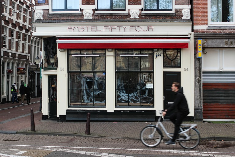 Cyclist passing Amstel Fifty Four - lively gay and lesbian bar in Amsterdam, Netherlands