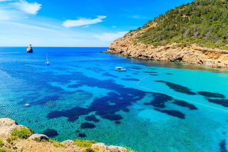 View of Cala Benirras bay with fishing boat on azure blue sea water, Ibiza island, Spain