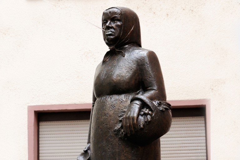Bronze statue of Frau Rauscher spitting water, Alte Sachsenhausen, Frankfurt, Germany.