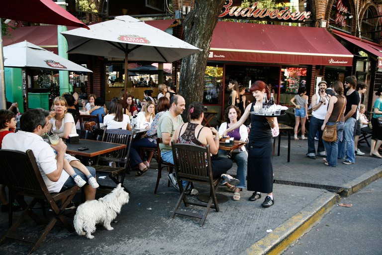 People sitting at an outdoors cafe at Plaza Serrano in Palermo Soho, Buenos Aires, Argentina.