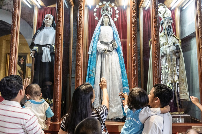 People praying in front of an statue of The Virgin Mary inside The Basilica Minore del Santo Nino, Cebu, Philippines