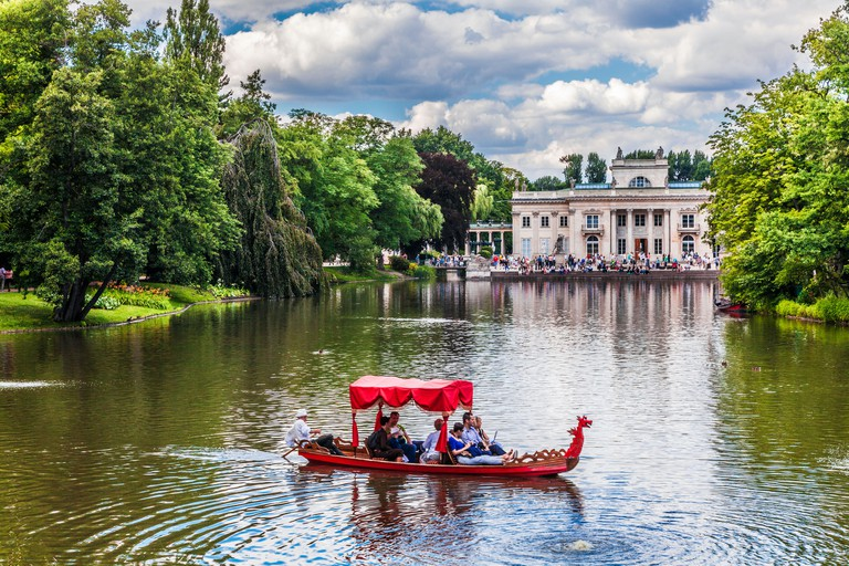 Tourists enjoy a gondola trip on the lake in Lazienki Park Lazienkowski, largest in Warsaw, with the Palace in the background.