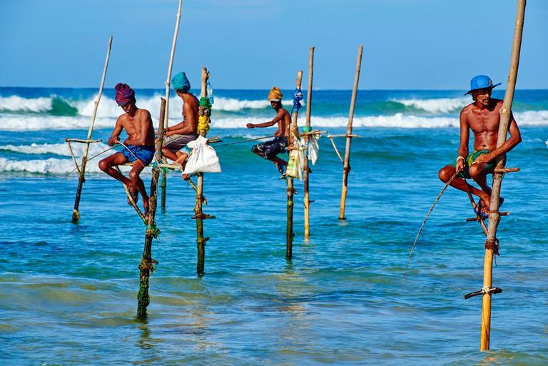 Sri Lanka, Southern Province, South Coast beach, Weligama beach, Stilt fishermen on the coast