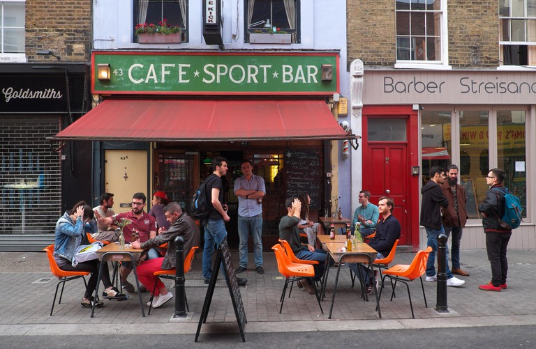 London street scene in Exmouth Market, Finsbury with customers enjoying a drink outside the Cafe Kick sports bar UK