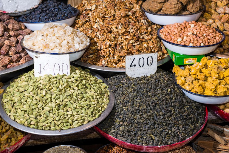 Cardamon, walnuts, peanuts, dates and black tea are displayed in bowls in the Old Delhi spice market
