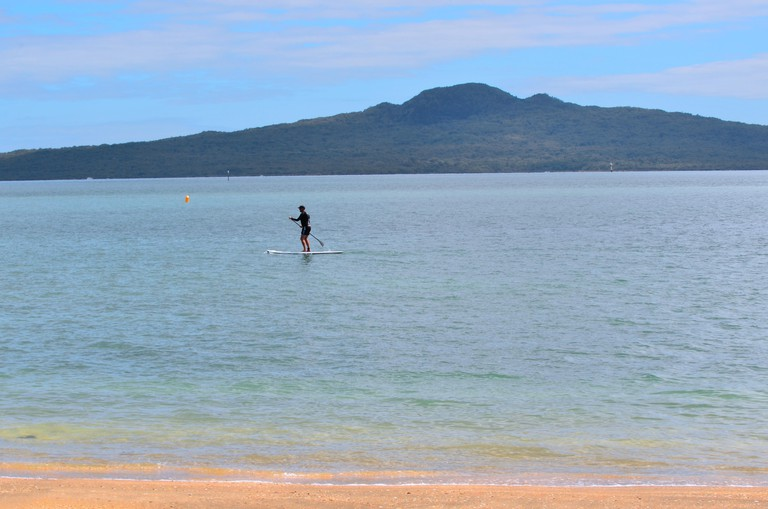 AUCKLAND - JAN 11 2016:Person paddle boarding in mission bay in Auckland New Zealand.It's an emerging global sport with a Hawaiian heritage.It's an ancient form of surfing for longer distances.