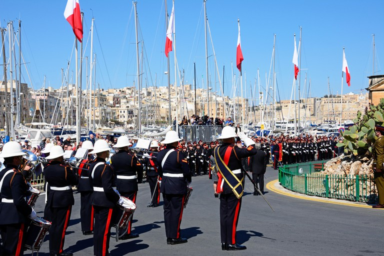 Freedom day celebrations with military personnel and a brass band by the Freedom Day monument, Vittoriosa, Malta, Europe.