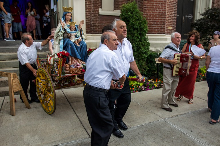 GN42K7 Three men move a Sicilian cart carrying a religious statue at the Little Italy Festival in Pittsburgh's Bloomfield neighborhood.