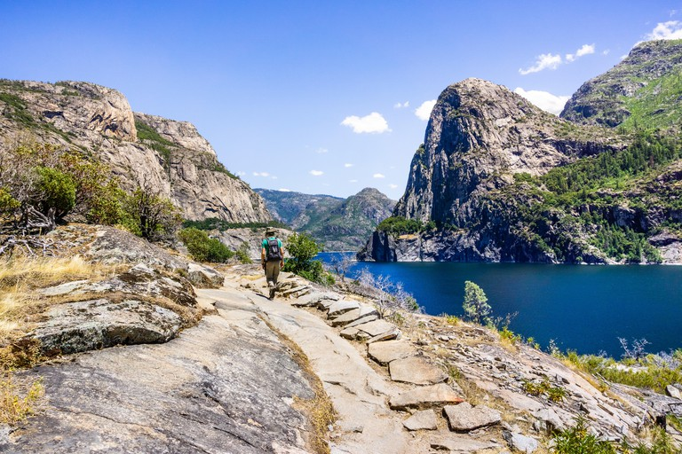 Hiking on the shoreline of Hetch Hetchy reservoir in Yosemite National Park, Sierra Nevada mountains, California; the reservoir is one of the main sou