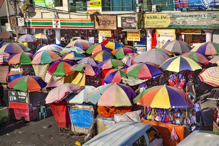 Colorful umbrellas shade buyers and sellers at the Baclaran open-air market in Manila, Philippines.