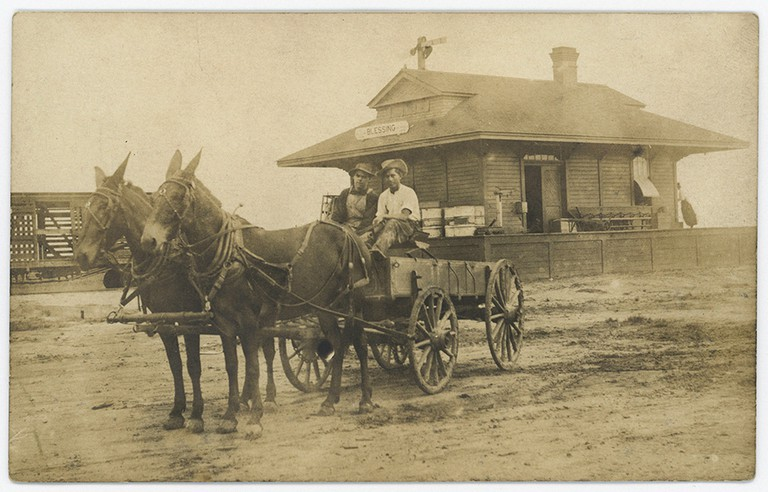 Two Men in Horse-Drawn Wagon at Train Depot, Blessing, Texas