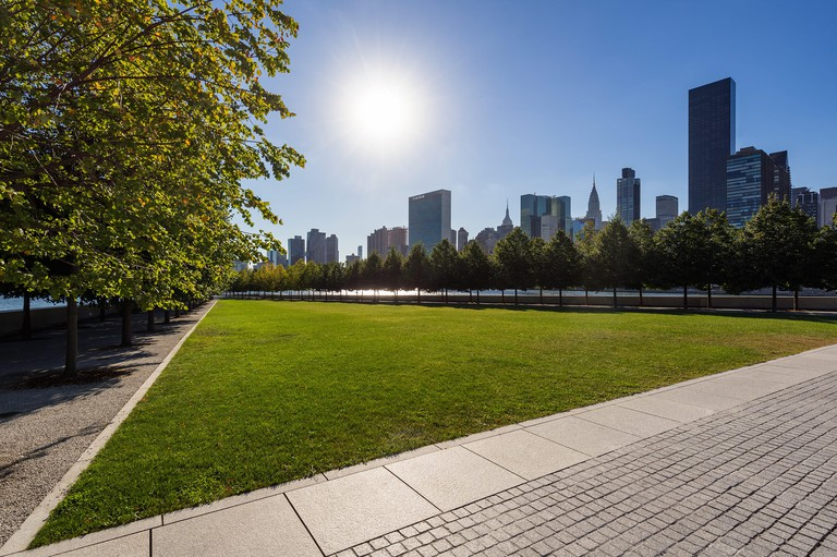 Summer view of Franklin D. Rosevelt Four Freedoms Park lawn with Manhattan Midtown East. Roosevelt Island, New York City