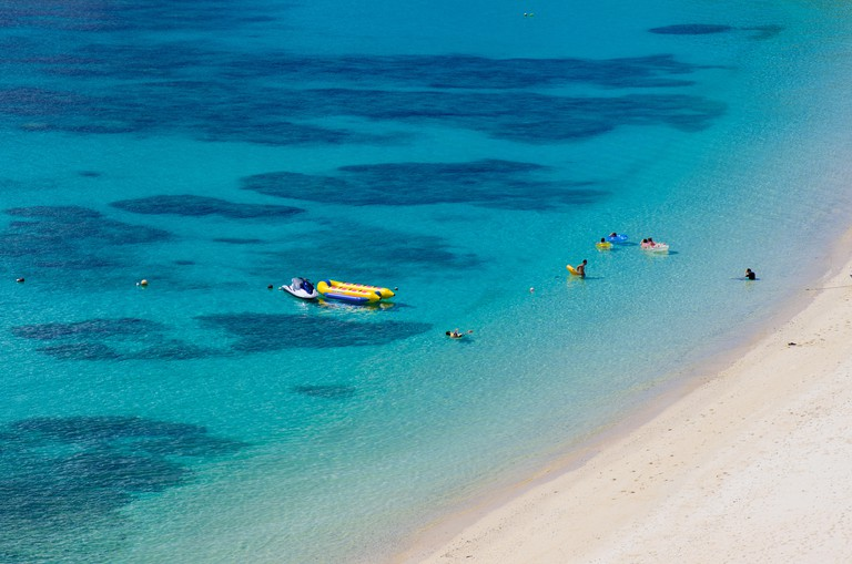 """The famous """"Kerama Blue"""" of Aharen Beach with people snorkeling among the corals on Tokashiki Island, Okinawa, Japan. Image shot 10/2014. Exact date unknown."""
