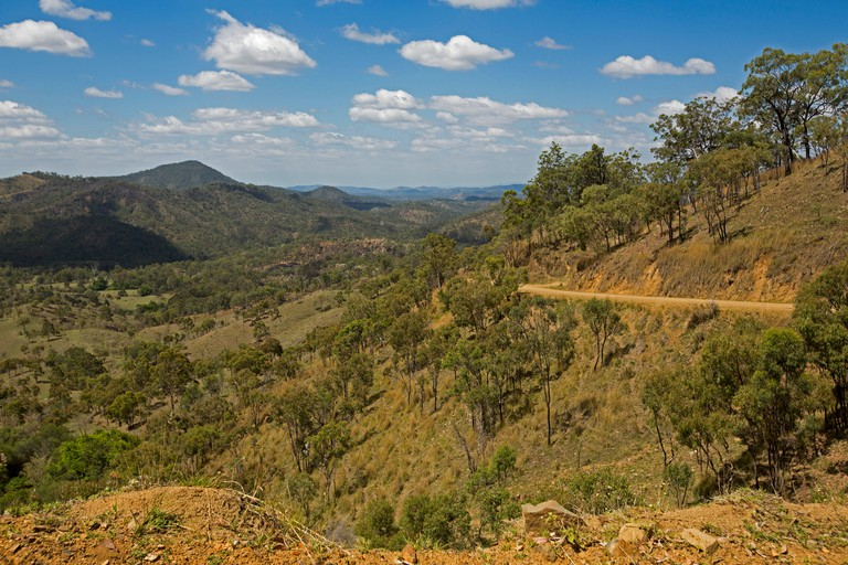 Australian landscape with extensive view of forested ranges, peaks, valleys of Great Dividing Range under blue sky
