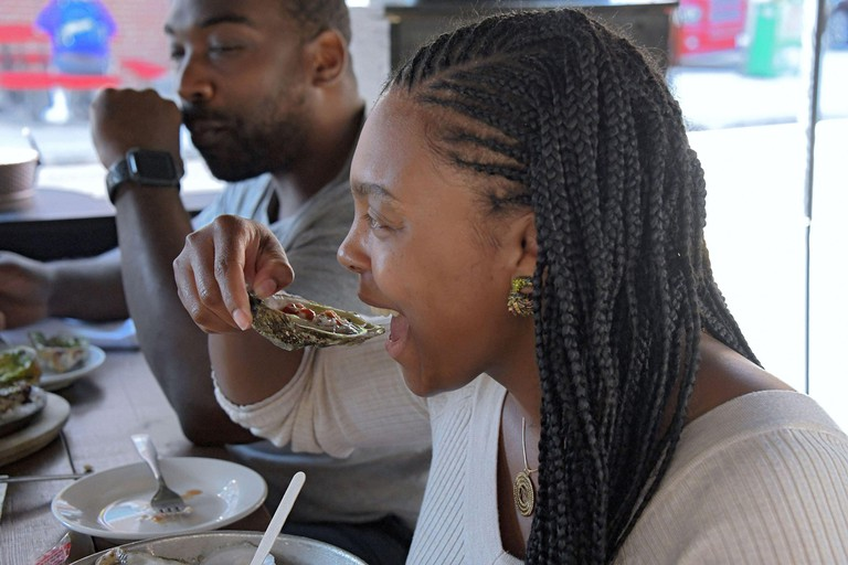 Latoria Shephard of Baltimore downs a raw oyster while sitting with William Gaskins, who ordered oysters Rockefeller at Mama's on the Half Shell in Canton. (Photo by Karl Merton Ferron/The Baltimore Sun/TNS/Sipa USA)
