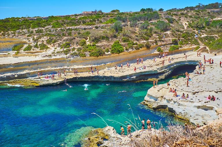 MARSAXLOKK, MALTA - JUNE 18, 2018: The holidaymakers enjoy sunbathing, swimming and snorkeling in St Peter's Pool - amazing limestone beach on Delimar