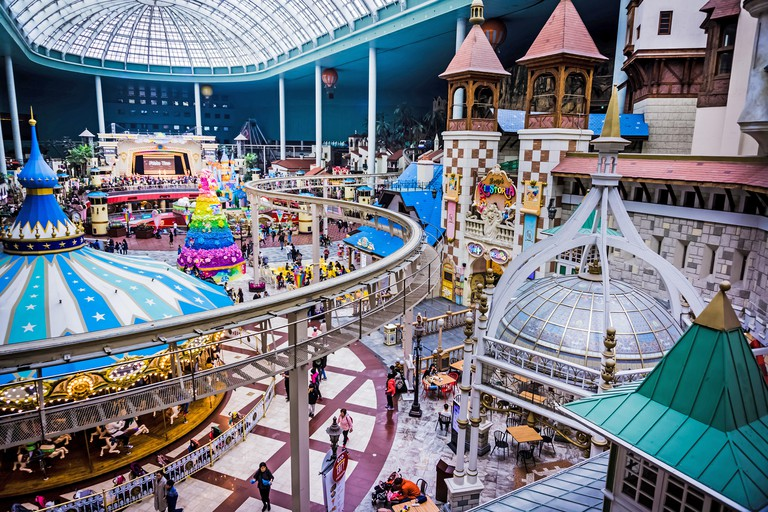 Seoul, South Korea - April 6, 2018: Roof of Carousel and flower tree view from far in Lotte World Adventure theme park .