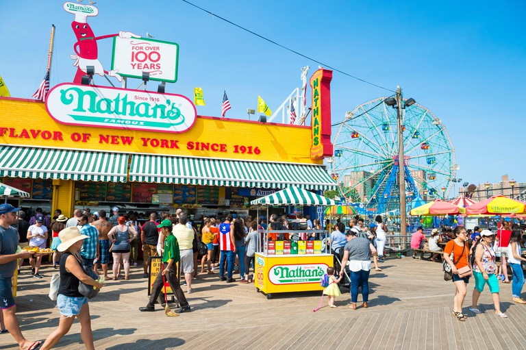 NEW YORK CITY - AUGUST 20, 2017: Visitors walk the iconic wooden Coney Island boardwalk outside the famous Nathan's hot dog stand on a hot summer day.. Image shot 08/2017. Exact date unknown.
