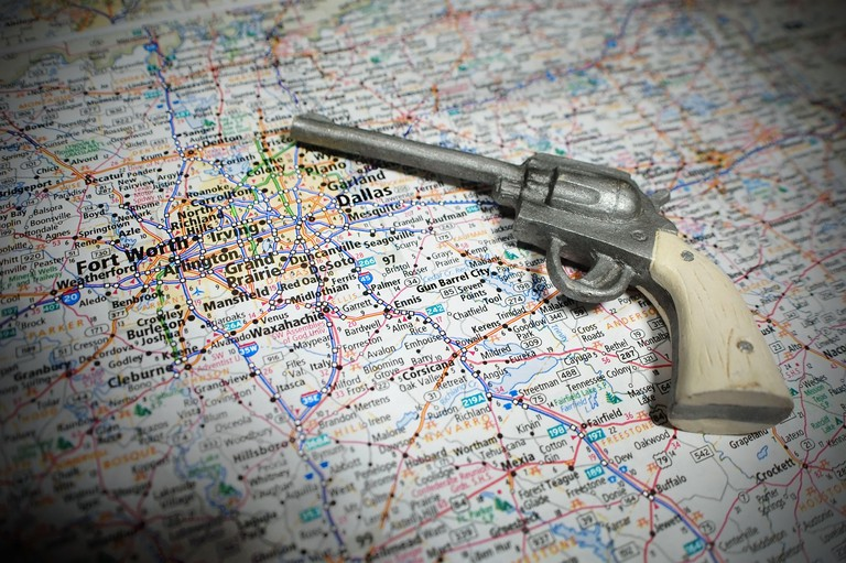 A toy pistol pictured with a map of Dallas Forth Worth and Gun Barrel City, TX.