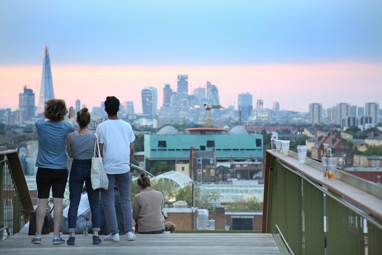 Young people view the London skyline at dusk from Frank's Cafe, the famous roof-top bar and restaurant on the multi-storey car park in Peckham, UK.