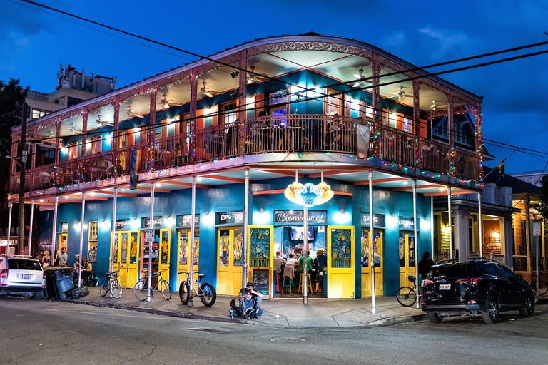 New Orleans, USA - April 22, 2018: Restaurant Dat Dog selling hot dogs with people sitting, eating, beggars on street, road at night, evening, blue ho