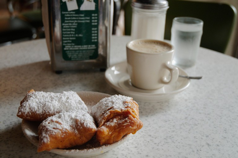 USA, Louisiana, New Orleans, Cafe du Monde, cup of espresso coffee next to icing sugar-dusted pastries on a table