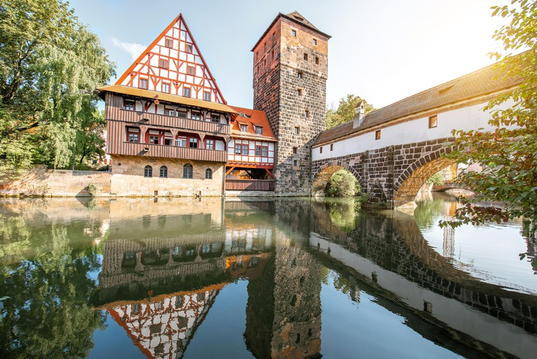 Beautiful landscape view on the riverside with old tower and house with reflection in Nurnberg during the sunrise, Germany