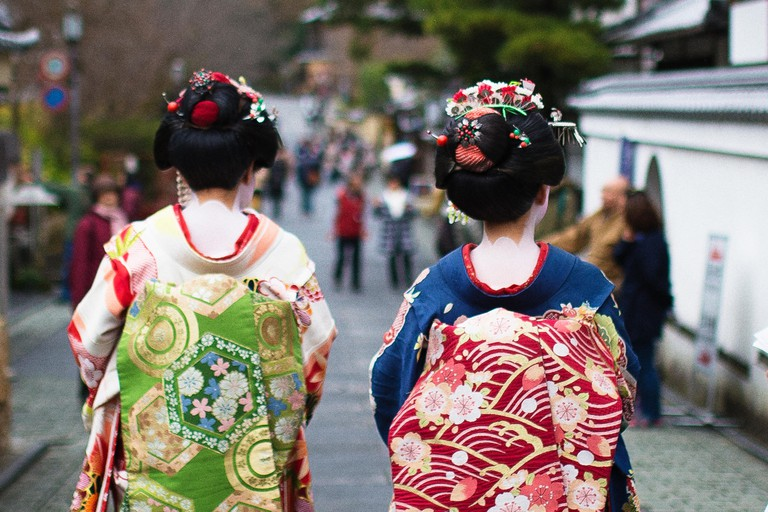 Two young geisha are walking on the way to Kiyomizu-Dera temple in Kyoto. Kyoto is the capital city of Kyoto Prefecture located in the Kansai region