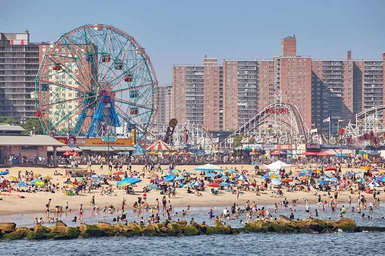 New York, USA - July 02, 2018: Crowded Coney Island beach and amusement park on a warm, hazy day.