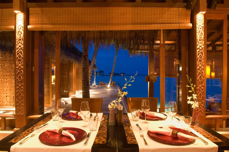A set table inside Reethi Restaurant at night, One & Only Resort Reethi Rah, Maldives