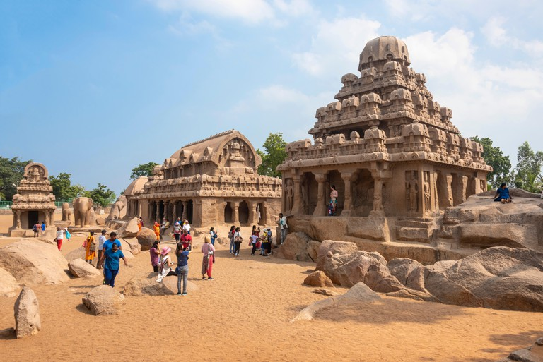 Pancha Rathas also known as Five Rathas or Pandava Rathas in Mahabalipuram with tourists and locals visiting on a sunny day with blue sky.
