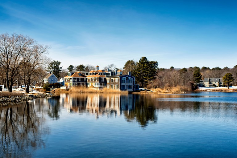 A large mansion reflecting off the waters of the Batson River in Kennebunkport Maine on a cold sunny winter day.