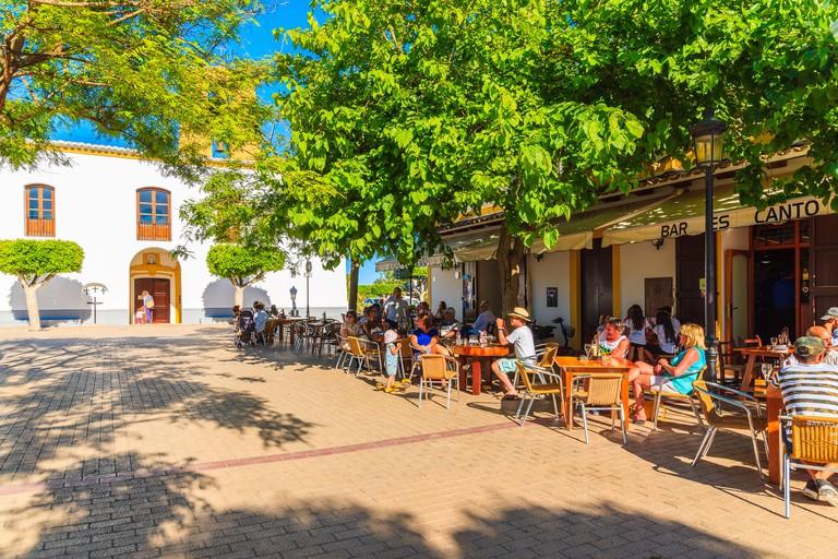 SANTA GERTRUDIS DE FRUTERA, IBIZA ISLAND - MAY 19, 2017: people sitting outdoors in restaurants on church square in Santa Getrudis town on Ibiza islan
