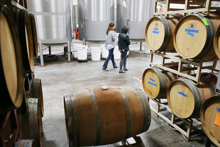 Napa, CA, USA. 14th Mar, 2015. General Manager Kristen Spelletich, right, walks through the warehouse with a guest, Dandy Noel, at Spelletich Family Wine Company in Napa during the Morning in the Winery open house, Saturday, March 14. © Napa Valley Regist