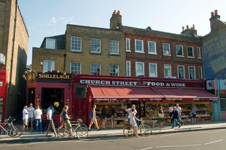 People on bycycles outside shop in Stoke Newington Church Street, Hackney London England UK